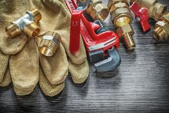 Pipe wrench connectors safety gloves water valves on wooden boar. D Stock Photo