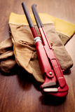 Pipe Wrench on Gloves Above the Wooden Table Royalty Free Stock Photography