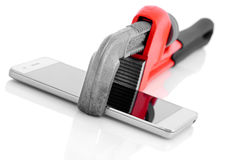 Pipe wrench holding smart mobile phone. Stock Images