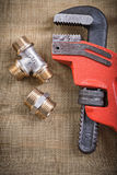 Pipe wrench plumbing fixtures on mesh filter grid Stock Photo