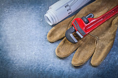 Pipe wrench protective gloves blueprints on metallic background Stock Photo
