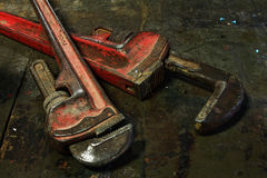 Pipe wrenchs. Pipe wrenches on old wood work bench Stock Images