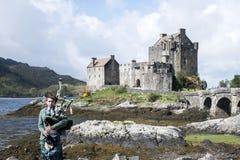 Pipebag球员前面爱莲・朵娜城堡小岛天空苏格兰英国20 05 2016年 免版税图库摄影