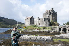 Pipebag gracza przodu Eilean Donan kasztelu wyspa niebo Szkocja Zjednoczone Królestwo 20 05 2016 Fotografia Royalty Free