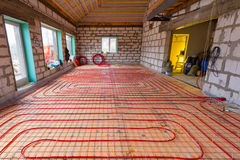 Pipefitter installing system of heating or underfloor heating installation. Water floor heating system interior. Plumbing pipes in apartment during under stock photo