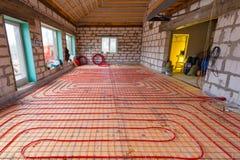 Pipefitter que instala el sistema de calefacción o de instalación de la calefacción por el suelo Interior del sistema de calefacc foto de archivo