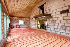 Pipefitter som installerar systemet av uppvärmning eller installation för underfloor uppvärmning Inre för system för vattengolvup royaltyfri foto