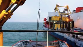 Pipelayaer platform crane lifts cable from deck of tug stock video footage