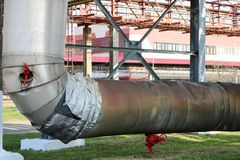 Pipeline estocad, large steam pipe in insulation made of fiberglass with red ventrals, fittings, valves, drainage with blue beams stock images