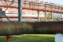Pipeline estocade, large steam pipe in insulation made of glass wool with red ventil, valve, valve, drainage at oil refinery, petr royalty free stock image