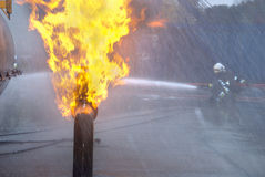 Pipeline fire with firefighters. Firefighters in protective uniform and helmet extinguishing pipeline and fuel tank fire with a hose and water jet in an Stock Images