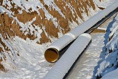 Pipeline laying in polymeric insulation in a trench dug. In the winter and covered with snow stock image
