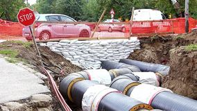Pipeline passes under the road. White sandbag bags are full with sand in wall formation to hold the Earth near traffic road. Industrially isolated pipes for stock video footage