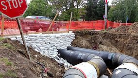 Pipeline passes under the road. White sandbag bags are full with sand in wall formation to hold the Earth near traffic road. Industrially isolated pipes for stock video