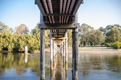 Pipelines running through underneath the walkway bridge across the river. stock images