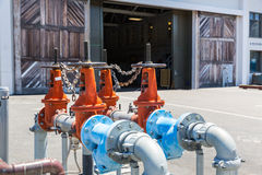 Pipelines, water pump and valves in dock. Pipelines, water pump and valves against open wooden gates of dock Stock Photography