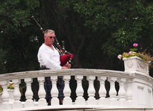 Piper And Bagpipes. Piper playing bagpipes on a balcony in summertime stock photos