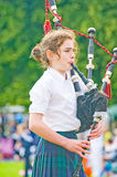 Piper in competition. An image of a girl playing the bagpipes in the competition at the annual Strathpeffer Gathering held on 6th August 2011 Royalty Free Stock Images
