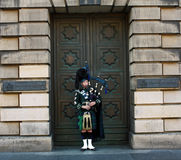 Piper in Edinburgh. EDINBURGH - JUN 9: A piper performs in front of the High Court of Edinburgh building during a summer festival. Taken June 9, 2009  in Stock Photography