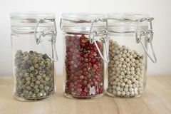 Piper nigrum fruit, white, green, pepper and Schinus molle, American false pink pepper and right green an white pepper. Three doses Stock Image