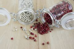 Piper nigrum fruit, white pepper and Schinus molle, American false pink pepper. Spilled on the wooden table Stock Image