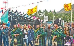 Pipers playing at Braemar Royal Gathering. Pipers awaiting the royal party at the gate to the main ring at the Braemar Highland Games with the English and Stock Photography