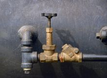 Pipes. Valves on steam boiler on wall Stock Photos