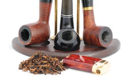 Pipes. Tobacco,  Lighter and Three Smoking Pipes on the Stand Royalty Free Stock Image