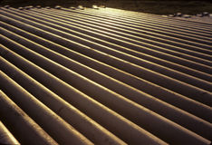 Pipes Backlight. Pipe yard for the storage and ready for delivery to drills sites Royalty Free Stock Images