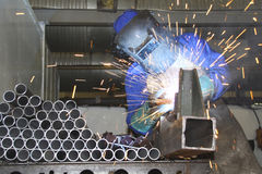 Pipes being welded by factory artisan. Factory worker arc welding on a production line of metal tubing, showing sparks flying Royalty Free Stock Images