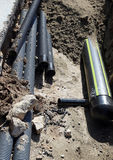 Pipes and a big gas pipeline inside the excavation in road const Stock Photography