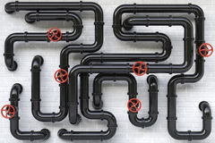 Pipes. Black oil pipes on a brick wall Royalty Free Stock Photography