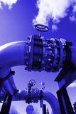Pipes, bolts, valves against blue sky in blue tone Stock Photo