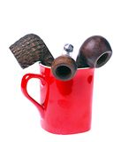 Pipes in cup. Old tobacco smoking pipes in red cup isolated on white stock image