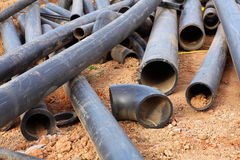 Pipes on dirt. Lots of polymer pipes cluttered in the dirt Stock Image