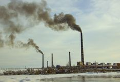 Pipes of the enterprise pollute the air with black smoke. Environmental pollution factory pipes smoke into the sky smoke soot stock photo