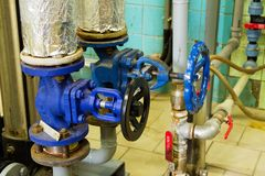 Pipes and faucet valves of heating system in a boiler room Stock Photos