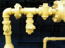 Pipes and Fittings. Yellow pipes and fittings in front of black glass windows Stock Photos
