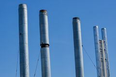 Pipes of gas boiler rooms on the background of blue summer sky. The smoke from the pipes does not go stock photos