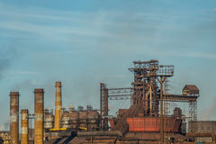 Pipes of heavy metallurgical industry pollute the air on background of the blue sky. Pollution of the environment. Fuming rusty Lipetsk Metallurgical Plant Stock Photography