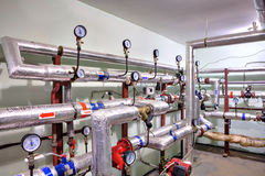 Pipes of hot water and heating with control devices. Royalty Free Stock Photography