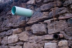 Pipes jutting out of stone wall. Waste Pipes jutting out of stone wall in over grown vines Stock Photography