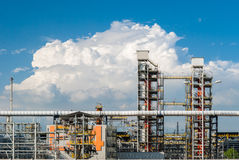 Pipes and machinery in a oil refinery. With blue sky and clouds in the background Stock Photos