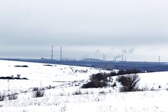 Pipes of metallurgical plant on a snowy horizon. Metallurgical plant - the enterprise of metallurgy, a plant with a full metallurgical production cycle. Mining royalty free stock photo