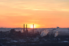 The pipes of the plant throw out toxic smoke at sunset. royalty free stock photo