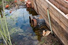 Pipes pollute the water. Rusty pipes pollute the water Royalty Free Stock Images