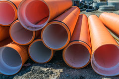 Corrugated water pipes of large diameter prepared for laying. Pipes of PVC large diameter orange color prepared for laying on construction site royalty free stock photo