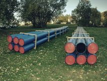 Pipes of PVC large diameter prepared for laying. On construction site. Colorful thick wall plastic pipe, blue light and red circle end cover royalty free stock photo