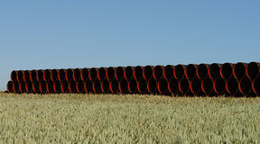 Pipes Red and Black. Pipes for a new gas pipeline wait on a field in the Palatine area of Germany Stock Images