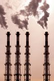 A group of pipes releases dark smoke steam vapor. environmental pollution, air pollution by toxic fumes. Pipes release dark smoke steam vapor. environmental stock images
